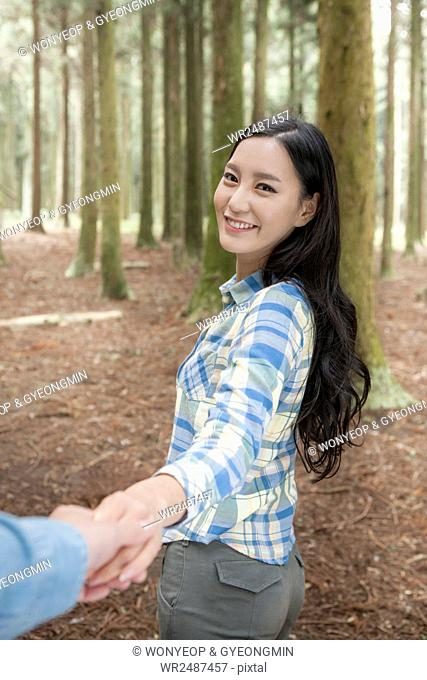 Side view portrait of young woman holding hands with a man in forest staring at front