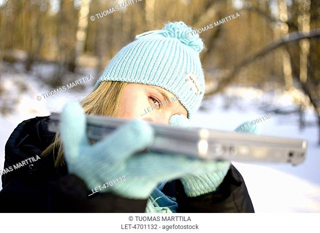 Woman with laptop computer outdoors in winter