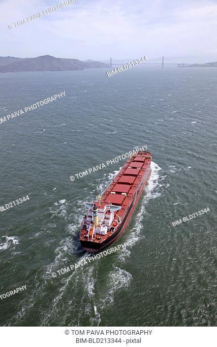 Aerial view of container ship in urban harbor, San Francisco, California, United States
