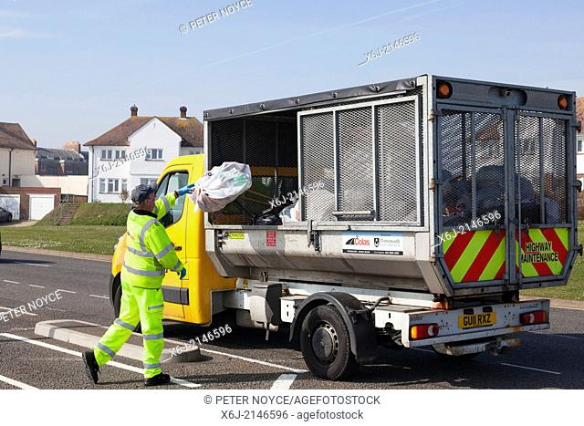 Council worker in high visibility clothing throwing rubbish into small refuse collection truck