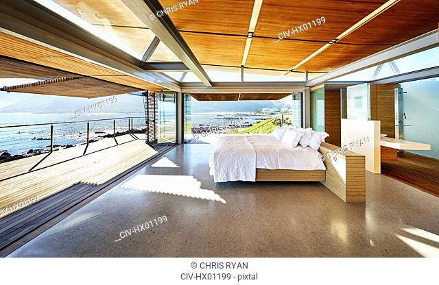 Modern luxury home showcase bed open to patio with sunny ocean view