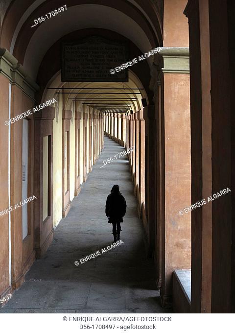 Woman walking under arcade, Bologna, Italy