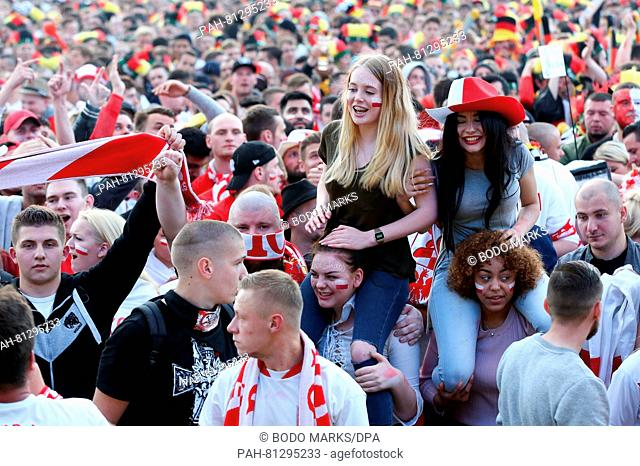 Soccer fans watch the soccer match Germany vs Poland at a public screening event at Heiligengeistfeld in Hamburg, Germany