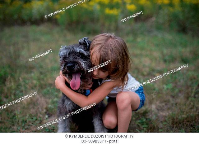 Little girl hugging pet dog on grass field