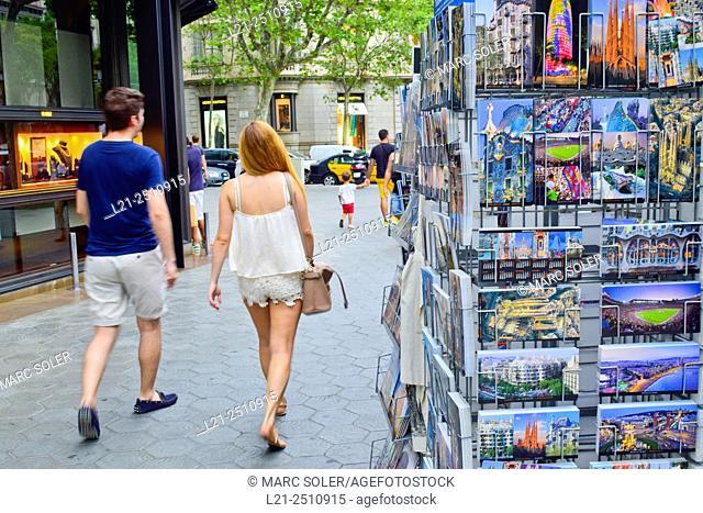 Postcards. Man and woman in summer clothes walking along street. Passeig de Gràcia, Barcelona, Catalonia, Spain