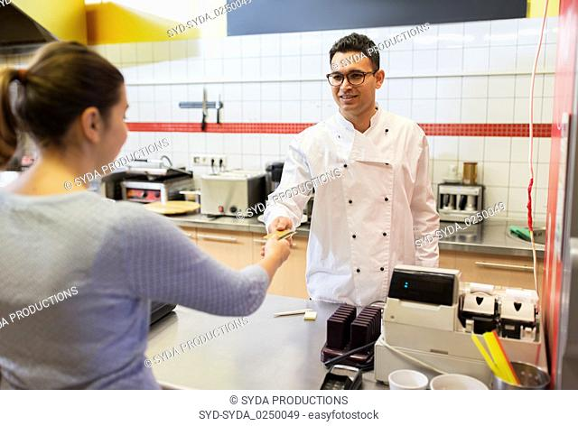 seller and customer paying at fast food restaurant
