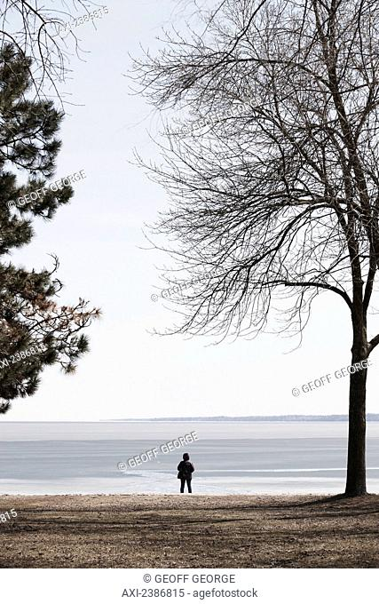 A person stands alone on the lakeshore; Barrie, Ontario, Canada