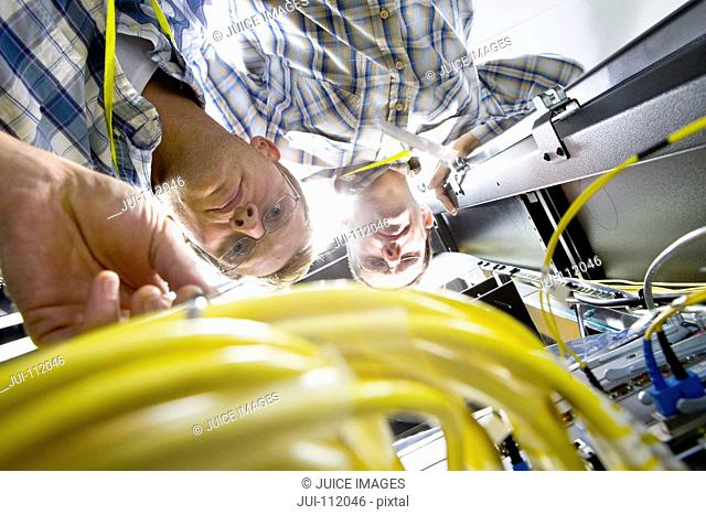 Technicians checking wiring of server in data centre