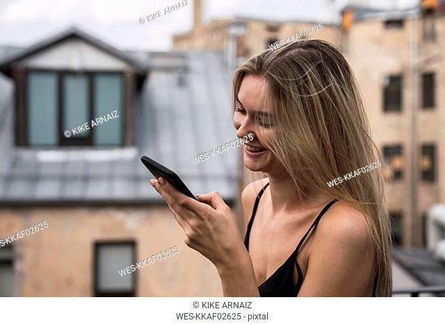 Smiling blond young woman on roof terrace looking at cell phone