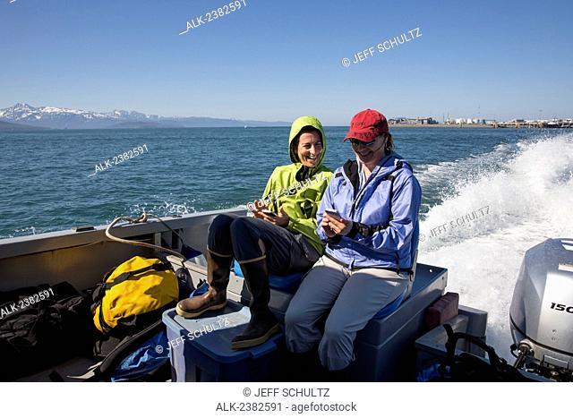 2 adult women use smart phones on stern of boat in Kachemak Bay near Homer, Alaska, Summer