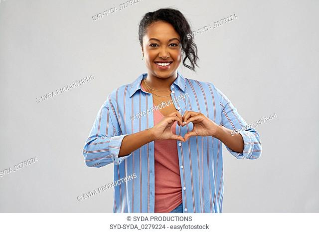 african american woman making hand heart gesture