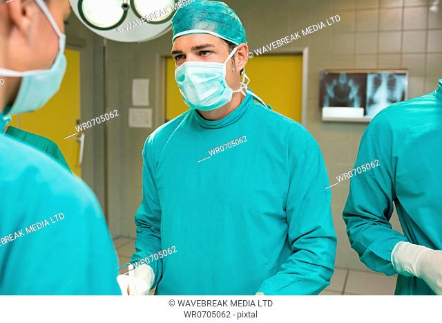Earnest surgeon looking at a nurse in an operating theatre