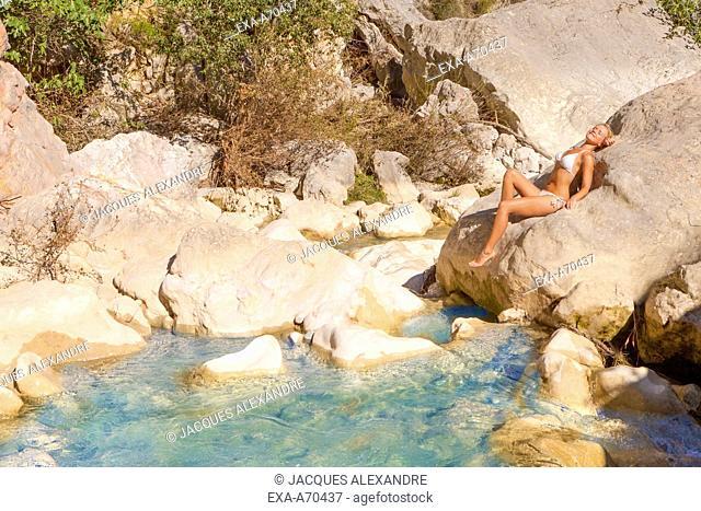 Woman sunbathing on rock at river