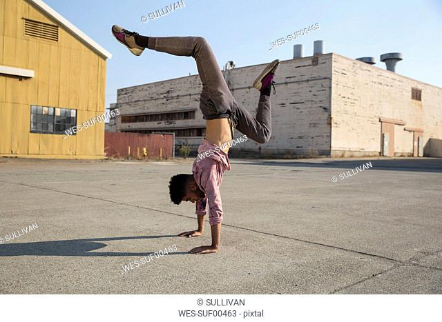Young man doing a handstand outdoors