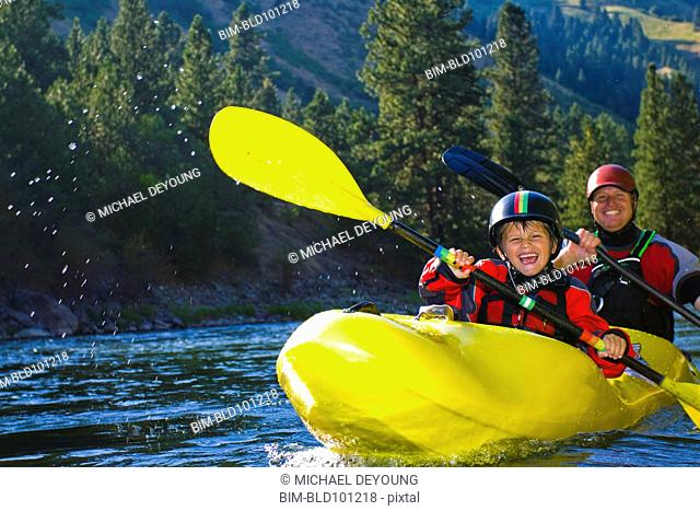 Caucasian father and son kayaking on river