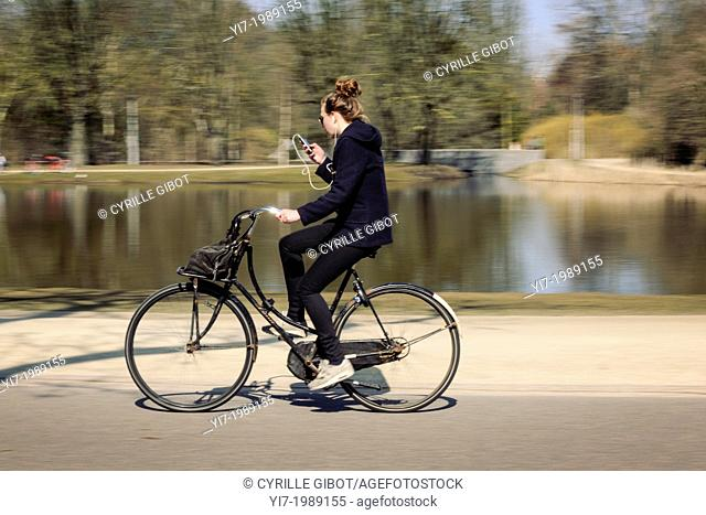 Young woman fiddling with her music player while cycling in Vondelpark public garden, Amsterdam, the Netherlands