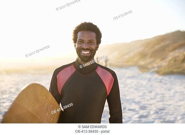 Portrait smiling, confident male surfer with surfboard on sunny summer beach