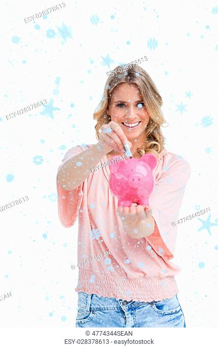 Smiling woman putting money into a piggy bank that she is holding against snow falling