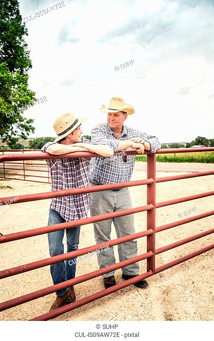Farmer and teenage grandson leaning against gate chatting