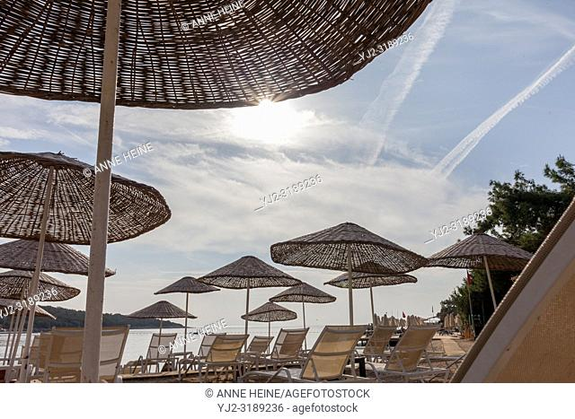 Sunshades and sun lounger at the beach with noone, low season in the morning. South of Bodrum, Turkey