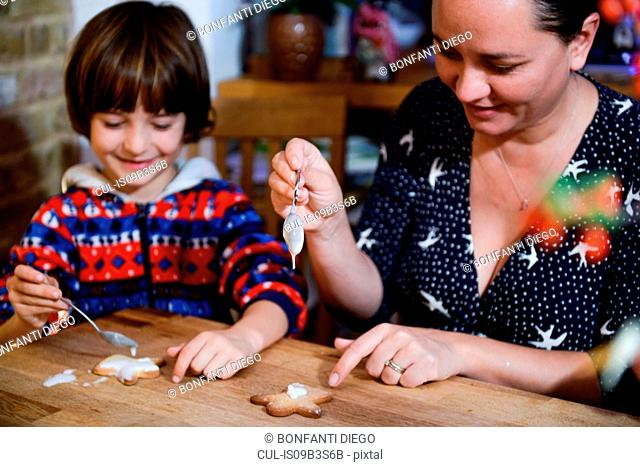 Mother and son at table icing home-baked Christmas biscuits