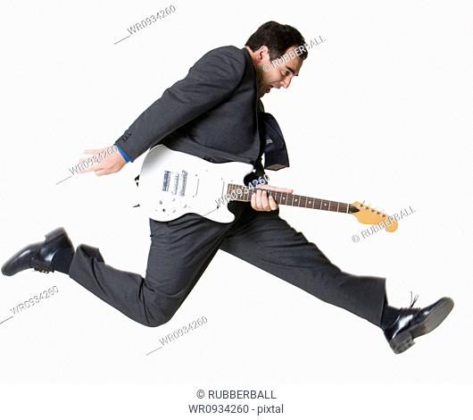 Businessman jumping with electric guitar