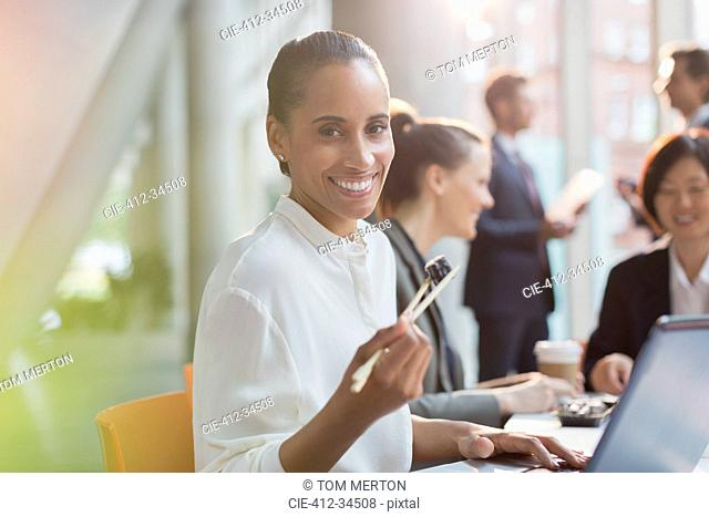 Portrait smiling businesswoman eating sushi lunch with chopsticks in conference room meeting
