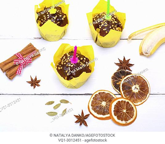 chocolate banana muffins with a candle on a white wooden background, top view