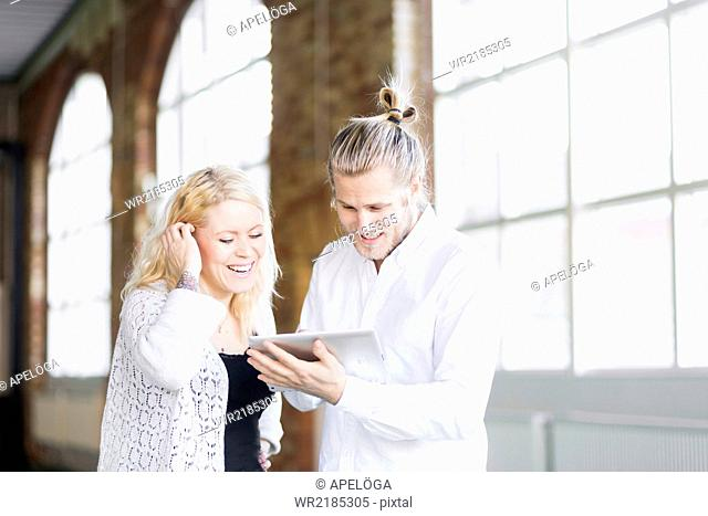 Happy man and woman using digital tablet in gym