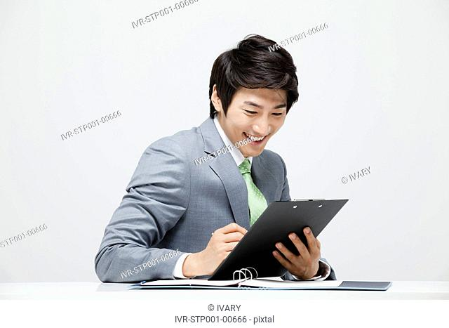 Asian Businessman Writing On Pad With Pen