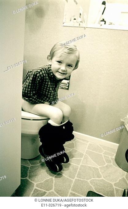 4 years old boy sitting on potty