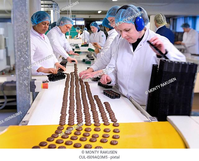 Workers on production line packing chocolates in chocolate factory