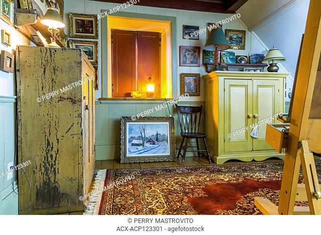 Artist's upstairs studio with closed wooden shutters on window, easel and paintings on the walls plus ocre and yellow antique wooden armoires inside an old...
