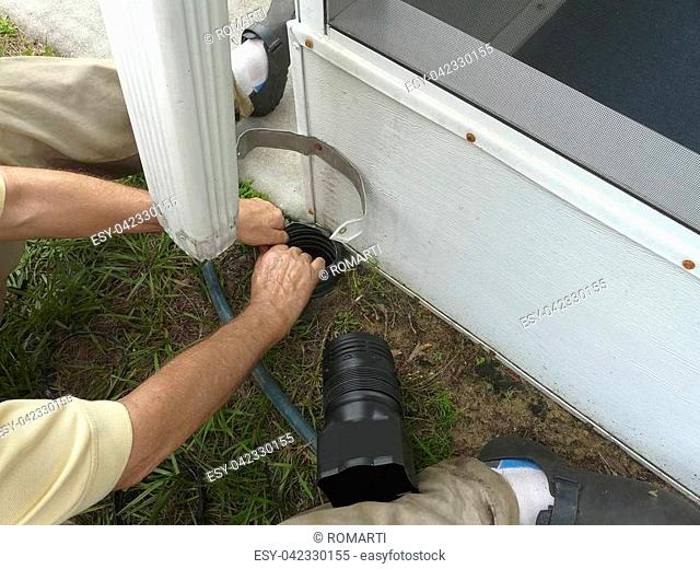 A man is installing a connector between the downspout and drainage pipe on his house to seal out debris and prevent foundation damage from water