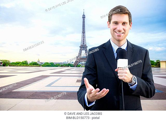 Caucasian news reporter talking near Eiffel Tower, Paris, France