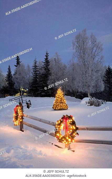 Split rail fence decorated with a Christmas wreath with a Christmas Tree in the background at dusk, Anchorage, Southcentral Alaska