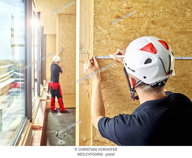 Worker with helmet marking with pencil on flakeboard