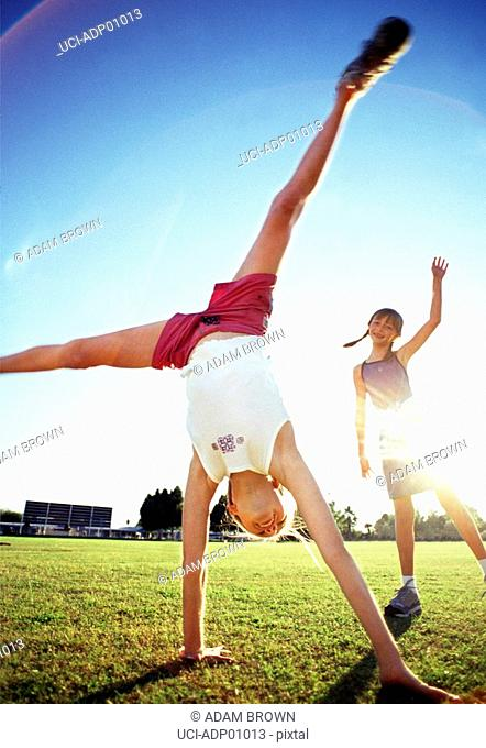 Girls doing cartwheels in sunlight