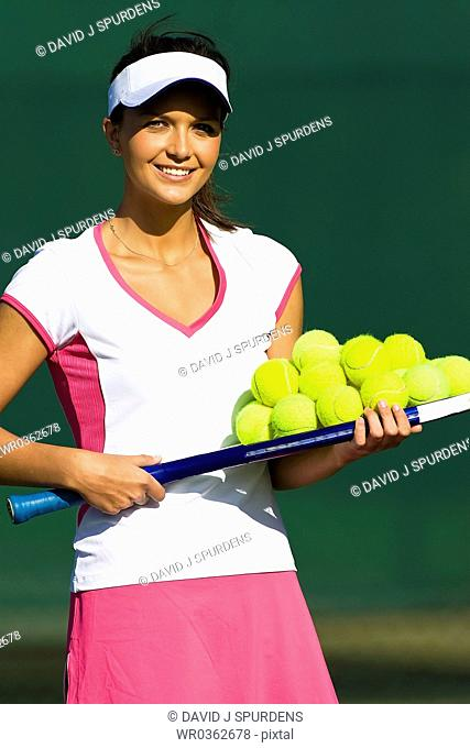 Tennis coach ready with tennis balls for coaching session