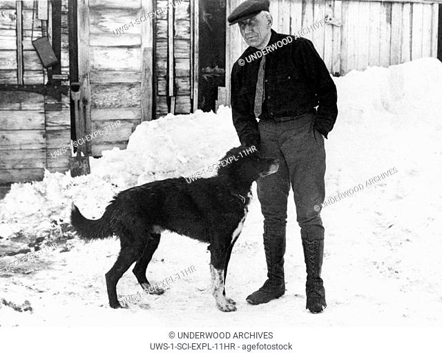 Candle, Alaska: July 5, 1923 Norwegian explorer Roald Amundsen with his lead dog outside a trapper's cabin at Candle, the last town on the route to Wainwright...