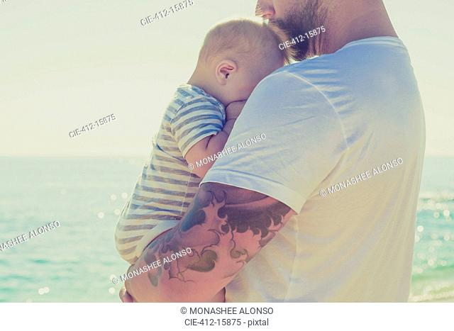 Close up of father holding baby son at beach