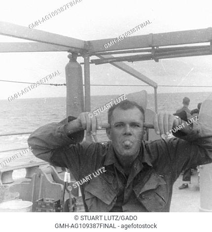 A United States soldier sticks his tongue out and makes a funny face while posing aboard a large ship, Vietnam, 1966