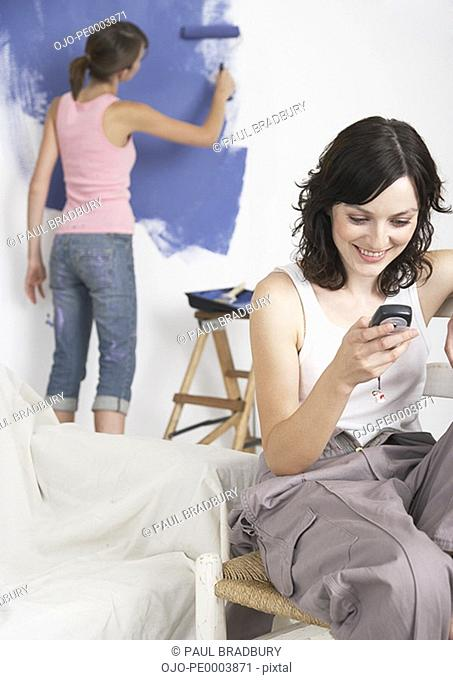 Woman looking at pda smiling with woman painting