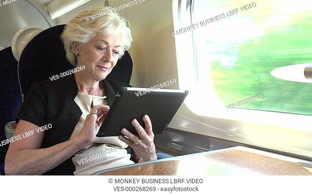 Senior businesswoman sitting at table working using digital tablet.Shot on Sony FS700 in PAL format at a frame rate of 25fps