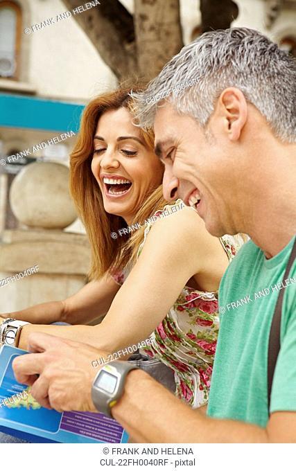 Happy couple reading guidebook