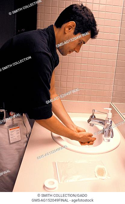 Photograph of a man rinsing his hands with water after washing them with soap, as part of smallpox post-vaccination care, 2003