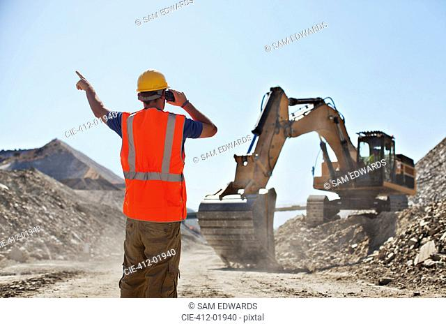 Worker directing digger in quarry