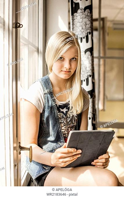 Portrait of girl holding tablet computer while sitting on window sill at school