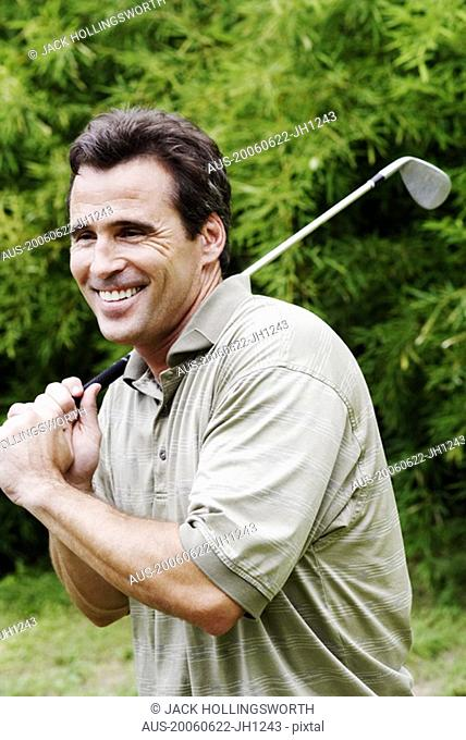 Close-up of a mature man holding a golf club and smiling