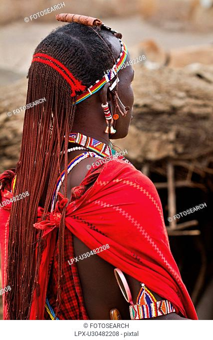 Close up side view of young Masai warrior moran, with long braided hair, wearing traditional red shuka and beaded jewellery, Amboseli, Kenya, East Africa